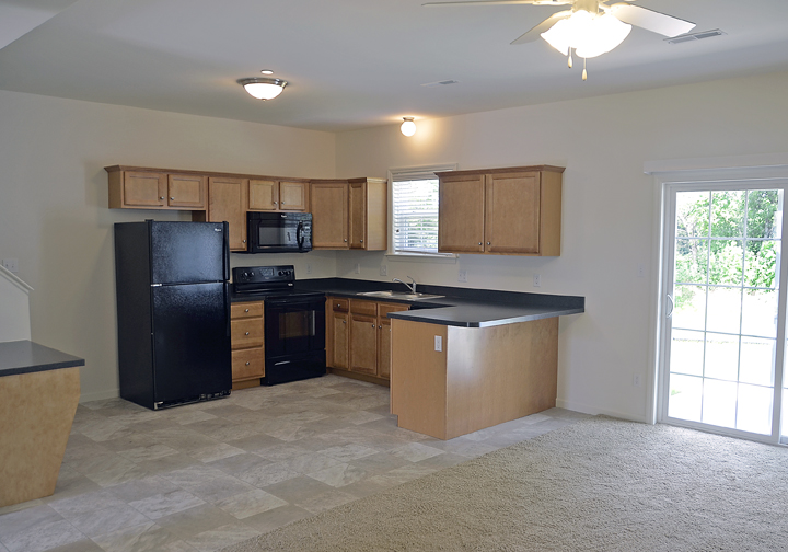 photo of unfurnished kitchen with black countertops and light wood cabinets